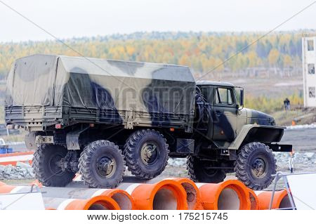 Nizhniy Tagil Russia - September 25. 2013: Army truck URAL-4320 jumps through obstacle on high speed. Display of fighting opportunities of arms and military equipment. Russia Arms Expo