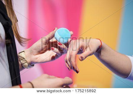 Women trying beauty gadget on their hands