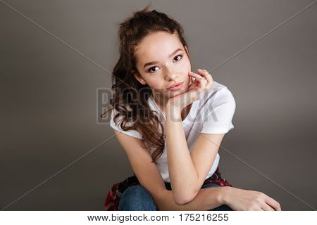 Close up portrait of a young pretty casual teenage girl looking at camera over gray background