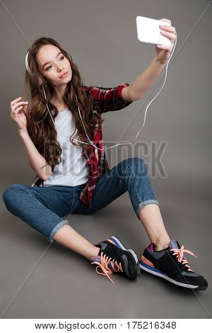 Young pretty girl sitting on the floor and taking selfie with headphones over gray background