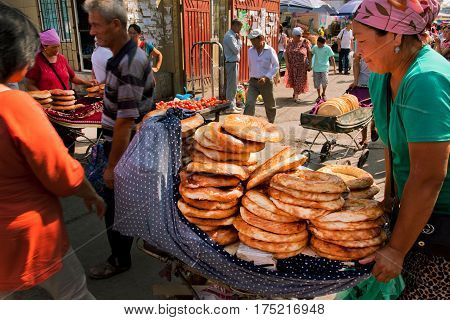 BISHKEK, KYRGYZSTAN - AUG 1, 2013: Women selling traditional Central Asian bread on the popular Osh market on August 1, 2013. In Kyrgyzstan 34 perc. are under age of 15 and 6.2 perc. are over 65.