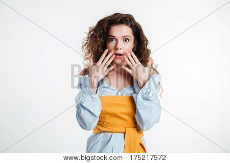 Portrait of an astonished casual girl holding hands at her face isolated on a white background