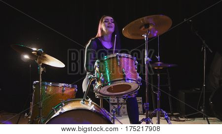 Teen rock music - attractive girl percussion drummer perform music break down, horizontal