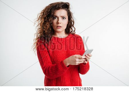 Portrait of an astonished young woman holding mobile phone and looking at camera over white background