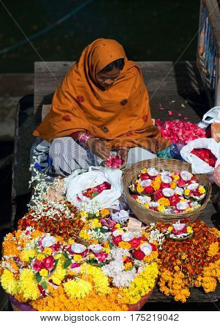 VARANASI, INDIA - JANUARY 3, 2016: Indian woman sitting on the ghats and selling pooja items for the offering - diya orange and yellow colored marigold flowers.