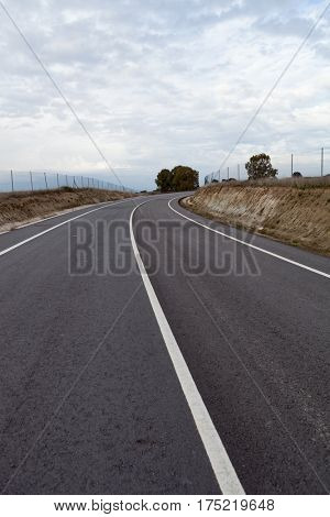 Lonely road with a cloudy sky of background