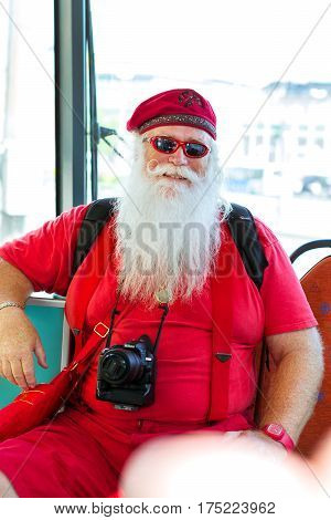 Helsinki Finland - August 5 2012: American Santa Claus in red summer suit with photo camera sitting in tram car. Stylish interior tram with comfortable seating. City public high-tech electric tram