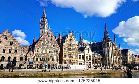 Ghent medieval city,  View of Graslei, Korenlei Streets, Korenmarkt, Post Office, Clock Tower over Leie river. Ghent, Belgium.