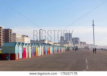 BRIGHTON, GREAT BRITAIN - FEB 28, 2017: Lots of very colorful bathing huts in Brighton and Hove and people walking in the background. February 28, 2017 in Brighton, Great Britain