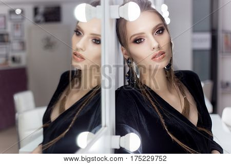 beautiful sexy girl with hair in the style of rock stands near the mirror in the dressing room in a black velvet gown with a bright spectacular evening jewelry with kriskalami sergt and ring