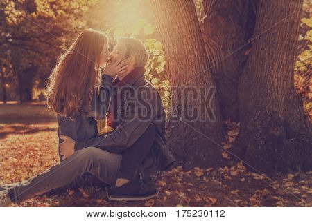 sunset couple kissing on a tree