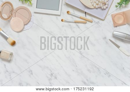 Feminine workspace on table desk with white smartphone lipstick; pearl necklace beige compact powder cosmetic brushes and pink nail polish on marble stone background; top view flat lay