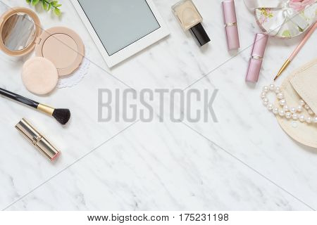 Feminine workspace on table desk with smartphone lipstick; pearl necklace compact powder cosmetic brushes and nail polish on marble stone background; top view flat lay poster