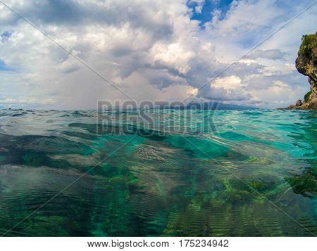 Oceanic landscape with transparent water and blue sky. Blue sea water look through. Double seaview above and below waterline. Clean water of tropical seashore. Summer vacation on exotic island photo