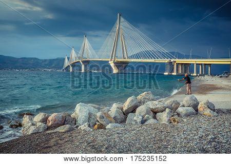 Patras, Greece - SEPTEMBER 2016: Fishermen on enbankmen near the Rio-Antirrio Bridge Charilaos Trikoupis