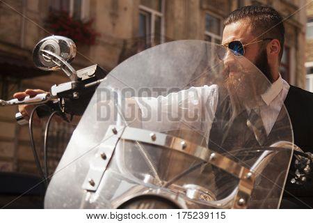 Serious Bearded Biker Man in black jacket sitting on motorbike outdoors