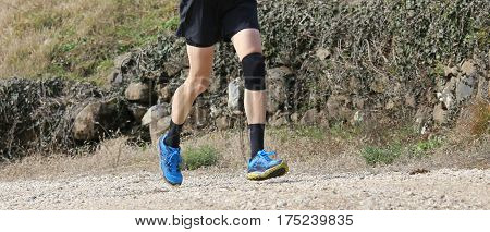 runner jogging during training with the sports and a knee brace on the bad knee