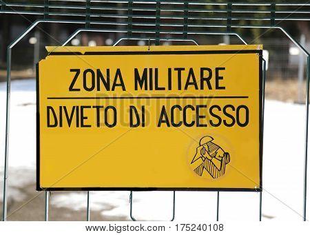 military area with the inscription ZONA MILITARE DIVIETO DI ACCESSO SORVEGLIANZA ARMATA which means MILITARY AREA PROHIBITION OF ACCESS ARMED SURVEILLANCE in Italian