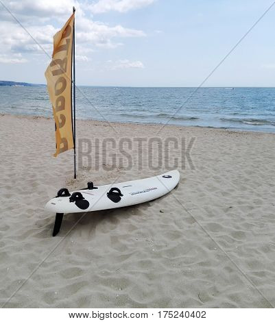 White windsurfing board lying on the banks of the sea The best place for learning windsurfing. Summer training wind surfing.