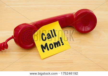 Remember to call your mother Retro red phone handset with a yellow sticky note and text Call Mom