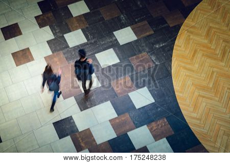 Two people walking in a public building hall top view. Motion blur technique of low speed shot. Blur silhouettes of people's. Low speed shutter shot.