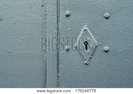 Rusty keyhole on gray metal door. Mortise lock on rivets in an old steel door painted with gray paint