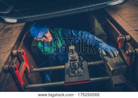 Car Mechanic Working Under the Car To Fix Vehicle Exhaust System. Car Maintenance.