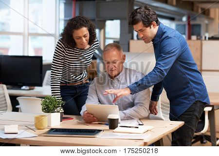 Diverse group of casually dressed professional colleagues talking business together over a digital tablet while having a meeting at a desk in a modern office