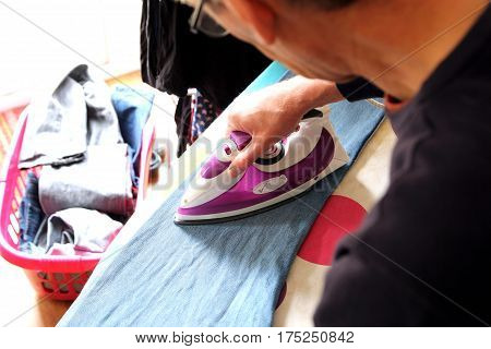 Older Man Getting To Grips With The Clothes Ironing For The First Time