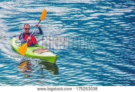 Kayak Lake Tour. Caucasian Men Paddling in the Kayak on the Lake.