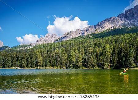 Scenic Kayak Touring on the Italian Alps Lake. Caucasian Outdoor Man in the Kayak.