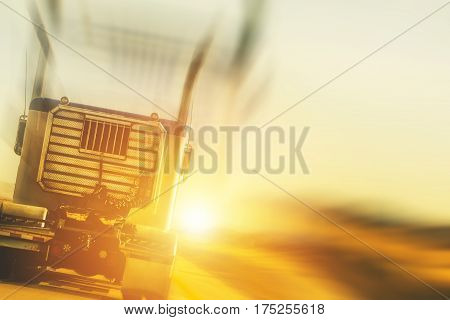 Trucking and Transport Concept Photo Background. Truck on the Highway During Sunset.