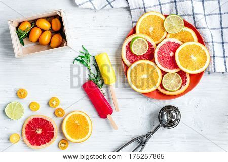 homemade ice-cream with sliced oranges and lime on stone table background top view