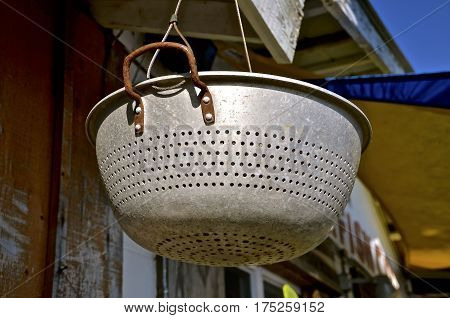 An old vintage colander hangs from the soffit of an old building