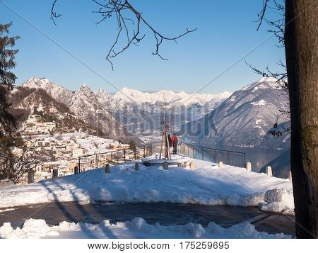 Monte Bré Switzerland - February 22. 2015: Winter landscape from Monte Bre. view of the village of Bré with two tourists who observe the view from a panoramic terrace.