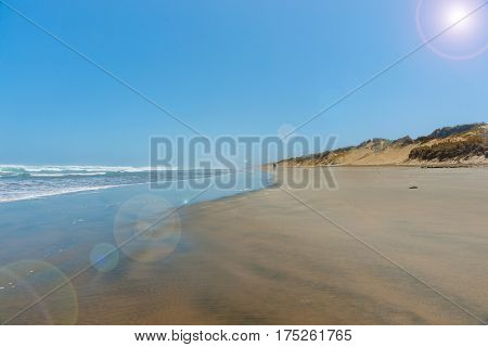 Lens flare above wide flat sand between dunes and sea at Ninety Mile beach Northland New Zealand