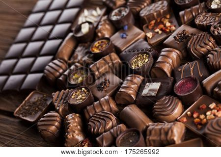 Chocolate bars and pralines on wooden background