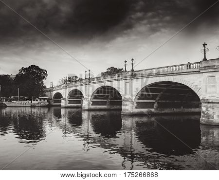 Black and white photo of Kingston bridge and its reflection over the water.