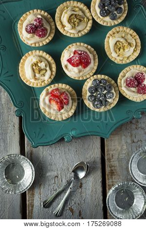 Blueberry, strawberry and pistachios tarts and spoons and empty aluminum plate on a wooden table