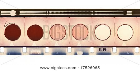 16mm vintage motion film strip sample with frames, soundtrack and six circles. Isolated on white background.