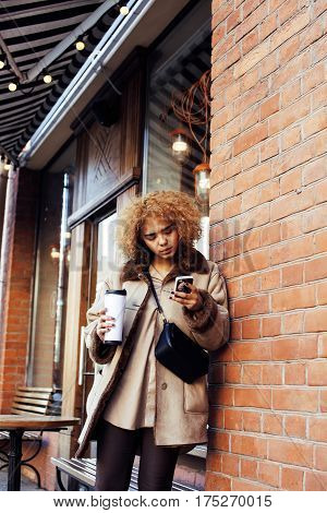 young pretty african american women drinking coffee outside in cafe, modern real business woman lifestyle concept