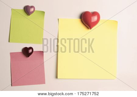 Three sticky note paper squares in green pink and yellow stuck to fridge door with heart shaped magnets. Left blank to provide copy space.