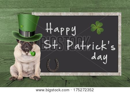 cute pug puppy dog with leprechaun hat for st. patrick's day smoking pipe sitting next blank chalkboard sign with horseshoe and shamrock on green wooden background