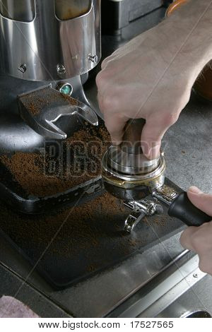Detail image of tamping espresso grounds into a bayonet