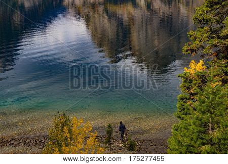 Person wearing hoodie on lake shore looking at reflections of mountains in the water
