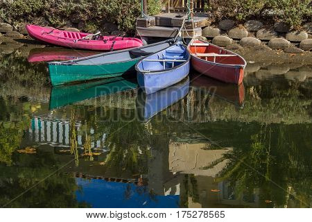 Colorful tethered row boats and canoe reflected in the canal water