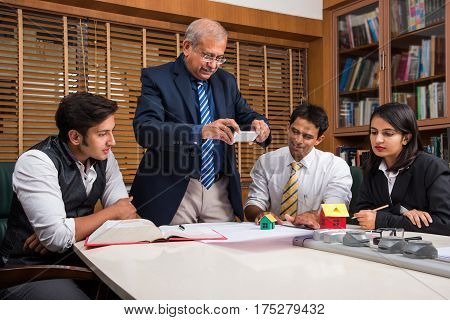 Indian Businessman or architect taking a picture of chart using smartphone while team members sitting in open space office. Selective focus.