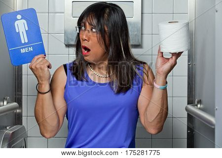 Transgender female in restroom stall with mens restroom and roll of toilet paper.