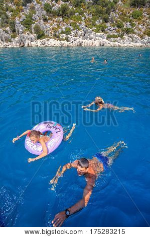 Antalya Turkey - 28 august 2014: Family of three white tourists bathing in blue sea water.