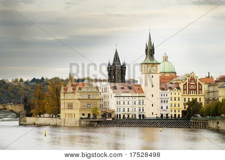The old town bridge and tower in the background behind some buildings in old town Prague